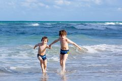 Two kid boys running on ocean beach. Little children having fun. Two happy little kids boys running on the beach of ocean. Funny cute children, siblings, twins royalty free stock photography