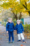 Two kid boys walking together in autumn park Stock Photos