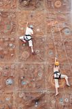 Two kid climbers. Kids competing on climbing wall Royalty Free Stock Photo