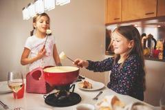 Kids eating fondue. Two kid girls eating swiss fondue for dinner stock photography