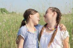 Two kid girls having fun on the field Stock Photos