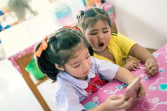 Two kid girls play mobile phone after school.  stock photo