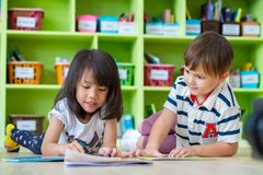 Two kid lay down on floor and reading tale book in preschool lib Royalty Free Stock Images