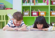 Two kid lay down on floor and reading tale book in preschool library,Kindergarten school education concept.  royalty free stock photo