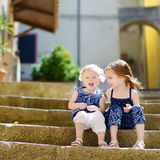 Two kid sisters sitting on stairs in italian town Royalty Free Stock Photography