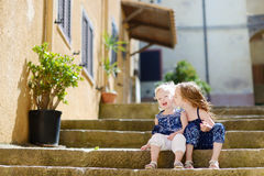 Two kid sisters sitting on stairs in italian town Royalty Free Stock Images