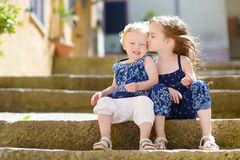 Two kid sisters sitting on stairs in italian town Stock Photos