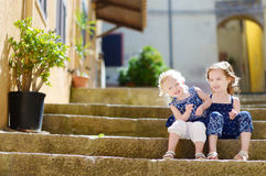 Two kid sisters sitting on stairs in italian town Stock Photography