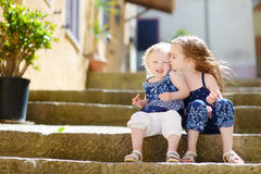 Two kid sisters sitting on stairs in italian town Royalty Free Stock Photo