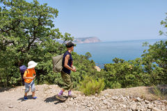 Two kids backpackers, boy n girl, walk next to sea Stock Image
