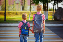 Two kids with backpacks walking on the road, holding. School tim. Two pretty boys with backpacks walking on the road, holding. School time Stock Photography