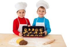 Two kids with baking on oven-tray Royalty Free Stock Images
