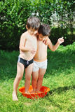 Two kids in basin. With water Royalty Free Stock Photography