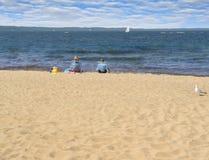 Two kids on the beach. Two children enjoy their beachfront view of the lake Stock Photos