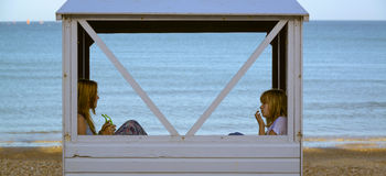Two kids in a beach hut stock images