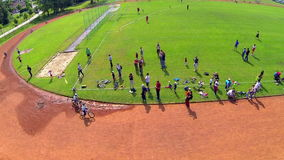 Two kids on bicycle finishing race first aerial shot. Flying over track with young kids cycle competition coming to end, parents cheering on finish line stock video
