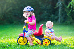 Two kids on a bike in the garden. Two happy kids, adorable curly toddler girl and a funny cute baby boy, brother and sister, playing together riding a bike royalty free stock photography