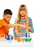 Couple kids in science lab. Two kids, black boy and blond girl in science chemistry class with test tubes and flasks, isolated on white Royalty Free Stock Images