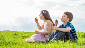 Two kids blowing up the soap bubbles on lawn stock footage