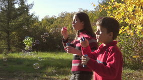 Two kids blowing up a soap bubbles, slow motion stock video