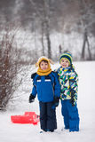 Two kids, boy brothers, sliding with bob in the snow, wintertime Royalty Free Stock Image
