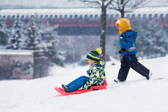 Two kids, boy brothers, sliding with bob in the snow, wintertime Stock Photo