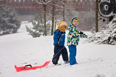 Two kids, boy brothers, sliding with bob in the snow, wintertime Stock Photography