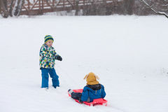 Two kids, boy brothers, sliding with bob in the snow, wintertime Royalty Free Stock Photography