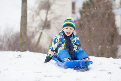 Two kids, boy brothers, sliding with bob in the snow, wintertime. Happiness concept royalty free stock photo