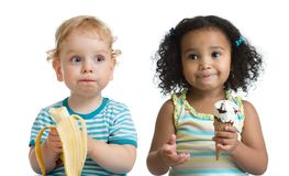 Two kids boy and girl eading fruit and ice cream Stock Photos
