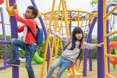 Two kids boy and girl having fun to play on children`s climbing Stock Photos
