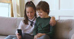 Two kids boy girl learning using smartphone together on sofa