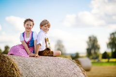 Two kids, boy and girl in traditional Bavarian costumes in wheat field Stock Images
