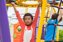 Two kids boy having fun to play on children`s climbing toy at sc Royalty Free Stock Photo