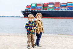 Two kids boys looking on container ship Stock Photo