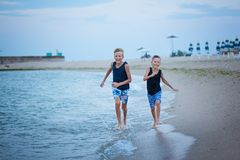 Two kids boys walking on sea beach summer, happy best friends playing stock images