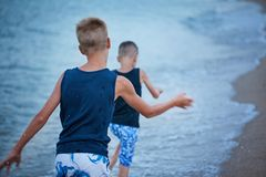 Two kids boys walking on sea beach summer, happy best friends playing. Back view stock photos
