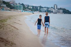 Two kids boys walking on sea beach summer, happy best friends playing. Back view royalty free stock images