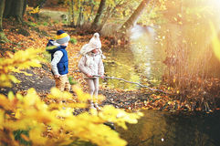 Two kids with branch near the pond royalty free stock photography