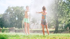Two kids, brother and sister, play with watering hose in summer garden royalty free stock image