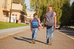 Two kids brothers with backpack holding on hands walking to school. Back view. Royalty Free Stock Photo