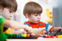 Two kids brothers play together at table Stock Photo