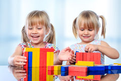 Two kids building with wooden blocks at table. Stock Photo