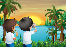 Two kids with a camera at the riverbank Royalty Free Stock Photography