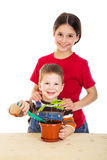 Two kids caring for potted plant stock photography