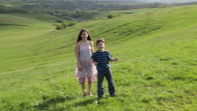 Two kids catch the soap bubbles on the hill. Two happy kids catch the soap bubbles on the green hill stock video