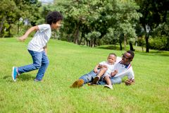 Two kids chasing and playing together while dad caught a boy in royalty free stock images