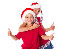 Two kids in Christmas hats together Stock Photo