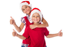 Two kids in Christmas hats together Stock Image