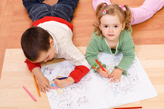 Two kids coloring on the floor Royalty Free Stock Photo